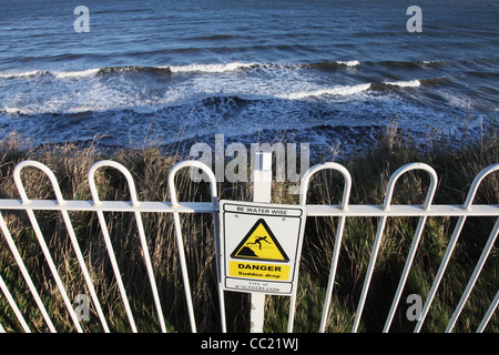 Sign or notice Danger Sudden Drop, be Water Wise, above cliffs Roker north east England, UK - Stock Photo