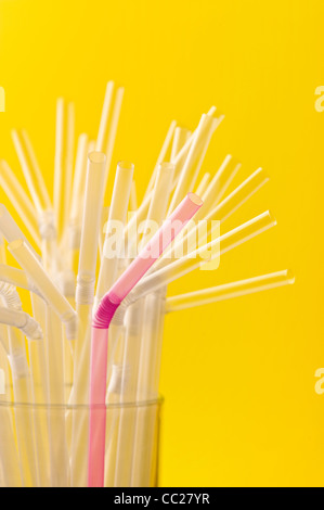 A pink straw amongst a group of clear straws