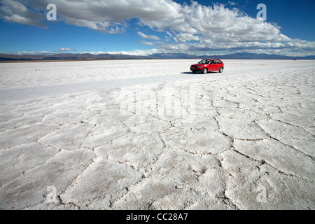 Red tourist car on the Salar Grande in the Jujuy province of Argentina - Stock Photo