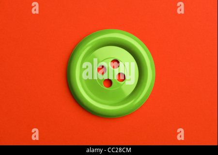 A green button on a red background - Stock Photo