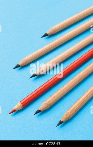 A red pencil amongst a group of lead pencils