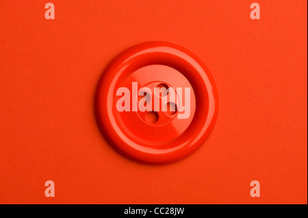 A red button on a red background - Stock Photo