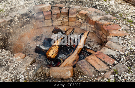 Ancient brick firepit with wooden logs smouldering - Stock Photo