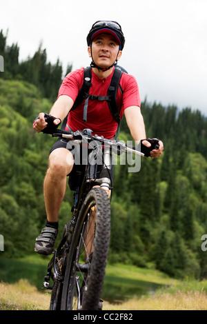 Asian mountain biker in summer mountain - Stock Photo