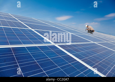 close up solar panel and professional worker installing photovoltaic solar panels - Stock Photo