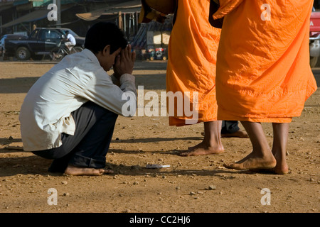 Buddhist monks are standing on a dirt road while receiving rice from a man in Ban Lung, Cambodia. - Stock Photo
