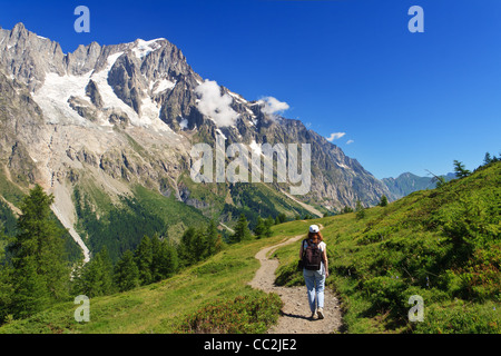 hiker in action in Ferret valley with Mont Blanc massif on background - Stock Photo