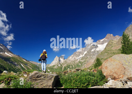 young woman stands on a rocks in Italian Alps - Stock Photo