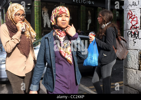 Two young Muslim women, in head scarves, walk along Brick Lane, in London's historic East End. - Stock Photo