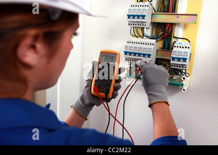 Female electrician checking a fusebox - Stock Photo