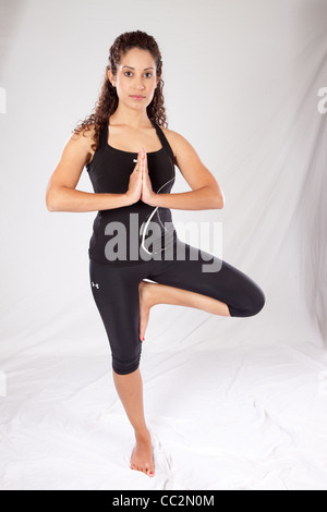 Lovely Caucasian woman standing on one leg in a yoga pose, while wearing a black exercise outfit and looking at - Stock Photo