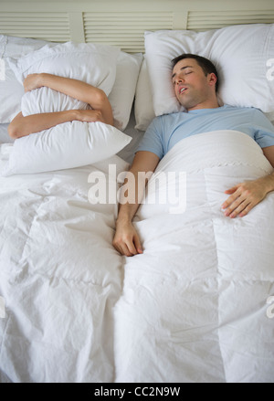 USA, New Jersey, Jersey City, Couple in bed, man snoring - Stock Photo
