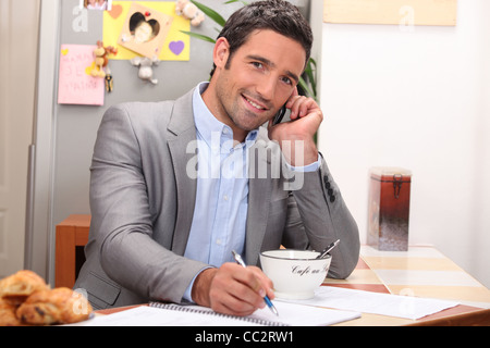 Man taking a business call over breakfast - Stock Photo