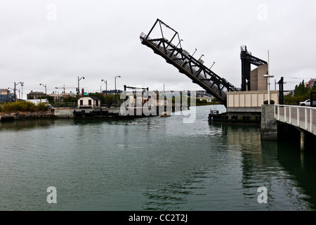 A sailboat, with sails furled, glides under the raised 4th Street Bridge along Mission Creek in San Francisco, California. - Stock Photo