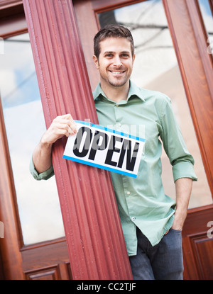 USA, New Jersey, Jersey City, Portrait of man with 'open' sign - Stock Photo