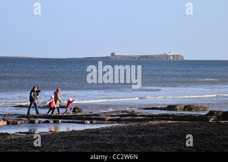 Young family walking on the beach at Bamburgh with the Inner Farne island in the background north east England UK - Stock Photo