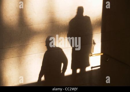USA, New York City, Shadow of two male pedestrians on sunlit wall - Stock Photo