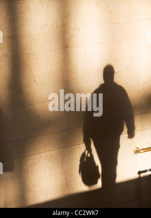 USA, New York City, Shadow of male pedestrian on sunlit wall - Stock Photo