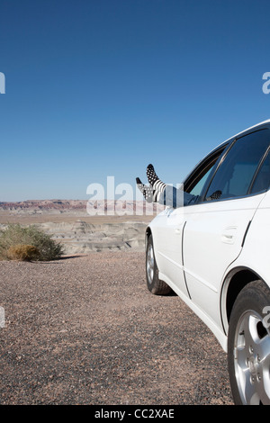 USA, Arizona, Winslow, Woman sticking feet out of car window parked in desert - Stock Photo