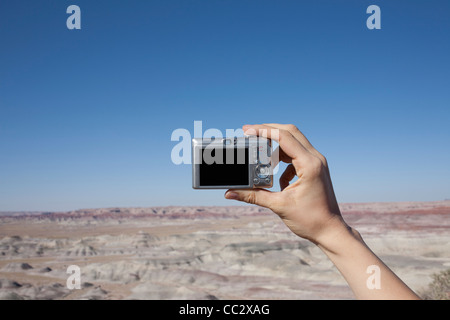USA, Arizona, Winslow, Hand of woman holding camera up against blue sky - Stock Photo