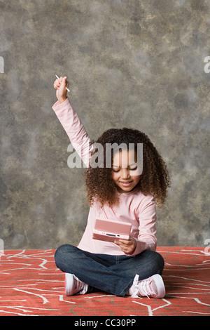 Girl (8-9) playing game, studio shot - Stock Photo