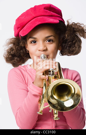 Portrait of girl (8-9) playing trumpet, studio shot - Stock Photo