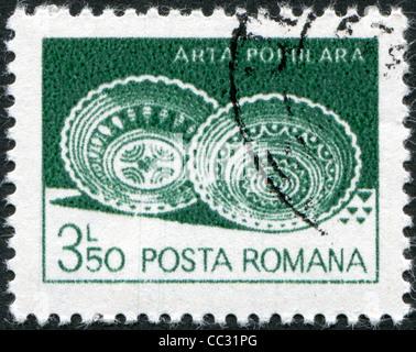 ROMANIA - CIRCA 1982: A stamp printed in the Romania, shows Ceramic plates from Leheceni, circa 1982 - Stock Photo