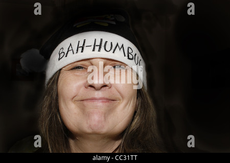 middle-aged woman wearing bah humbug hat - Stock Photo