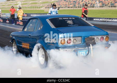 Australian Lee Sanders performs a tire smoking burning rubber burnout in his Mazda RX3 rotary engined drag racing - Stock Photo