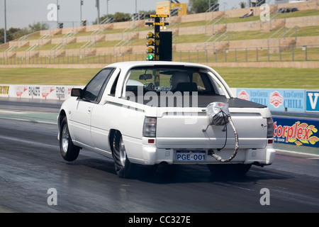 Australian drag racing Holden Commodore ute pick up truck launches hard on the green light and lifts the front wheels. - Stock Photo