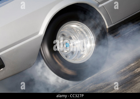 spinning wheel of a drag racing car skidding and producing burning rubber tire smoke. - Stock Photo