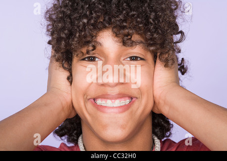 Portrait of teenage boy (14-15) covering ears with hands - Stock Photo