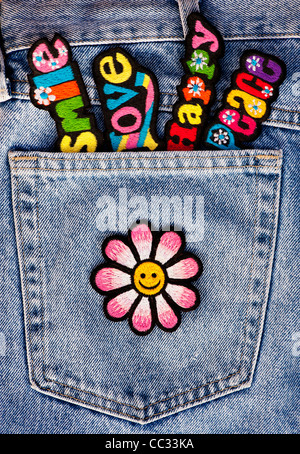 Embroidery iron on patches of Multicoloured Love, Peace, Happy words with a smiley face flower in a denim pocket - Stock Photo