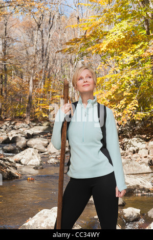 USA, New Jersey, Female hiker standing by stream in forest - Stock Photo