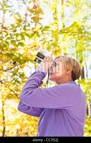 USA, New Jersey, Woman looking through binoculars in Autumn forest - Stock Photo