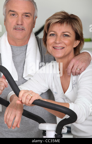 Couple working out in a gym together - Stock Photo