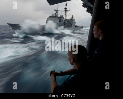 Ticonderoga-class guided-missile cruiser USS Bunker Hill (CG 52) take on fuel in heavy seas during a refueling at - Stock Photo