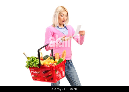 A surprised woman looking at store receipt and holding a shopping basket - Stock Photo