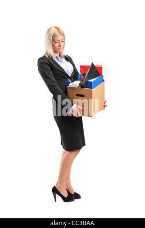 Full length portrait of a fired businesswoman in a suit carrying a box of personal items - Stock Photo