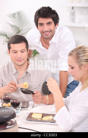 Sharing a raclette. - Stock Photo