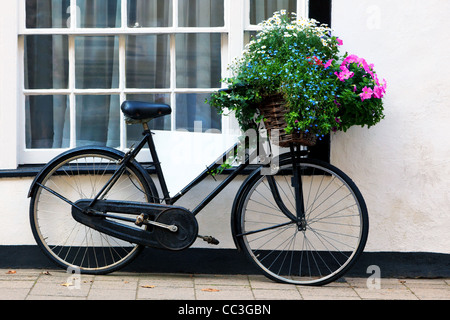 Photo of an old bicycle with a basket full of flowers and a blank advertising board in the frame. - Stock Photo