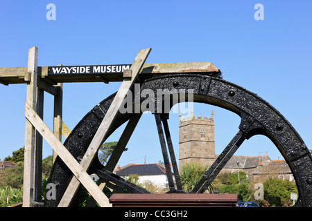 Zennor Cornwall England UK. Trewey Mill working water wheel outside Wayside Museum with village church of St Senara - Stock Photo