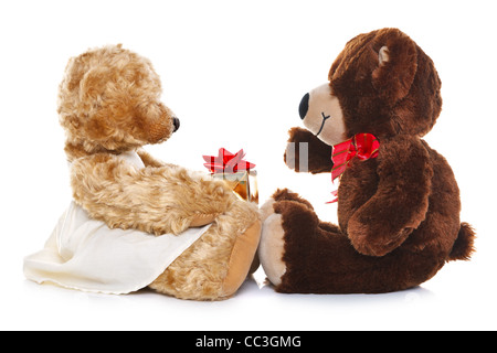 Photo of a boy teddy bear giving a girl teddy a gift, isolated on a white background. - Stock Photo
