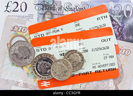 Two UK train tickets for Standard off-peak value travel out and return with sterling money banknotes and coins. - Stock Photo