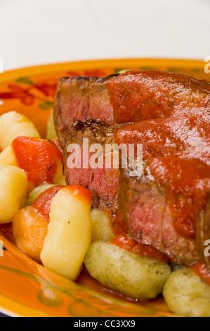 Steak with Tomato Sauce on top of Potato, Spinach, and Tomato Gnocchi - Stock Photo