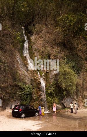 India, Arunachal Pradesh, Yazali, family washing car and showering in Himalayan mountain waterfall - Stock Photo