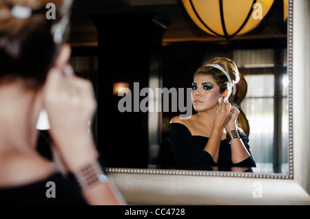 A woman in evening attire putting on her earrings looking in a mirror - Stock Photo