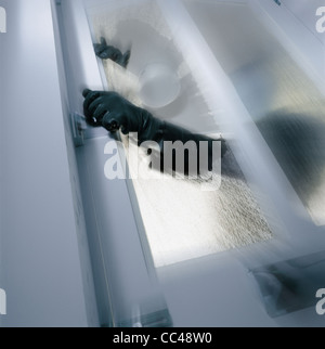 silhouette of the criminal opening door - Stock Photo