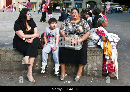 buxom Mexican grandmother with plump daughter & chubby young grandson sitting on a wall at edge of Zocalo next to - Stock Photo