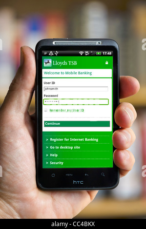Logging on to mobile banking with the Lloyds TSB app on an HTC smartphone - Stock Photo